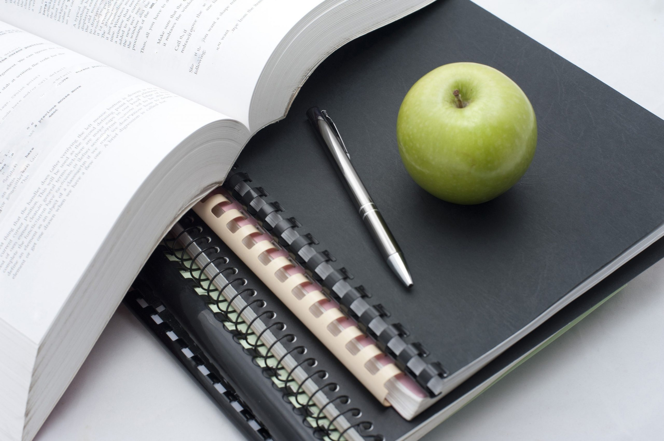 Conceptual background for school reading and studies with a fresh juicy green apple and pen lying on spiral bound notebooks alongside an open book
